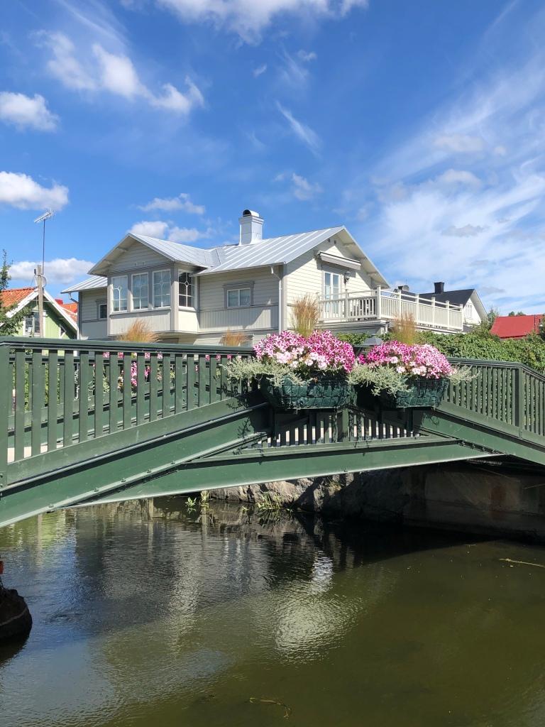 Vackra hus och en bro med blomdekorationer, vid Trosaån.