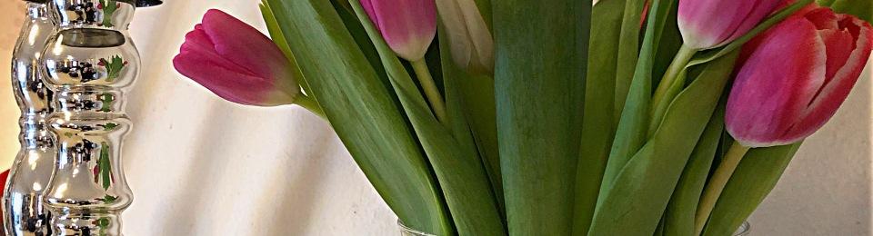 Tulpaner i vas och silvriga ljusstakar