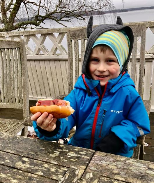 Minstebror äter korv med bröd på altanen
