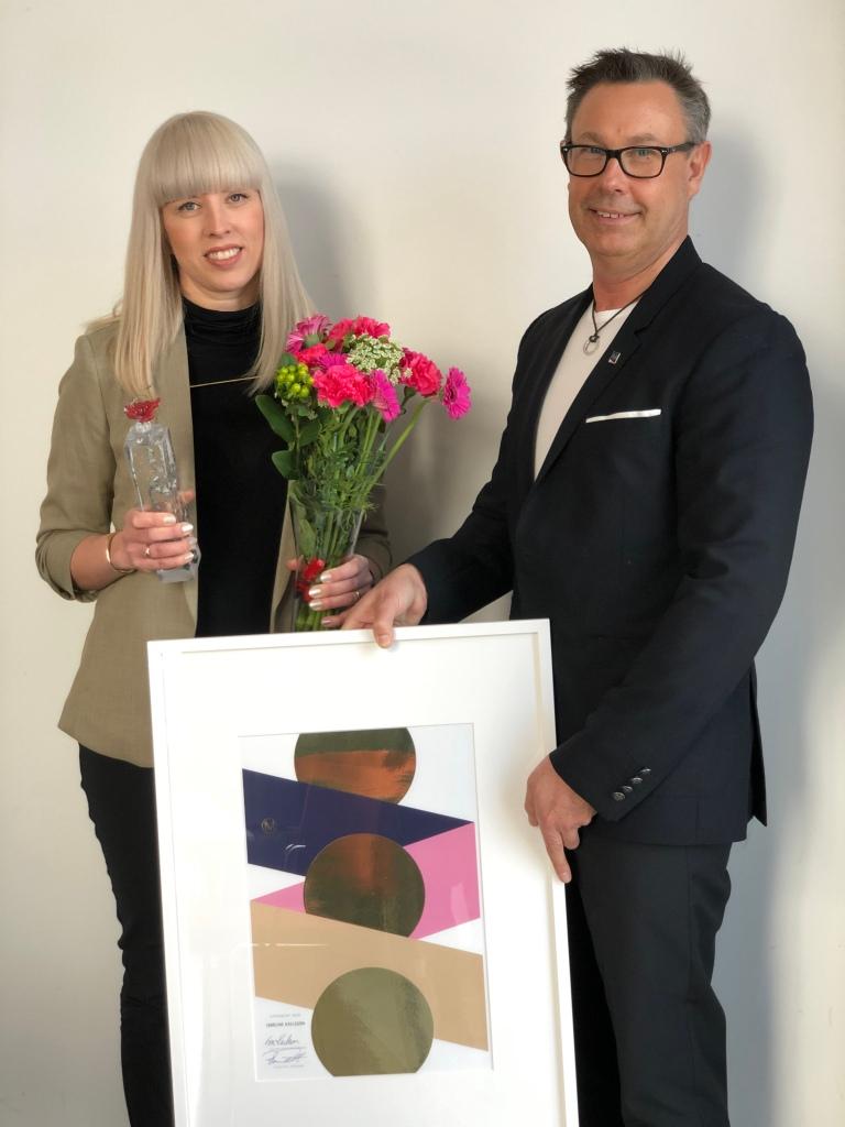 Caroline Axelsson och Roger Pihl med diplomtavla, skulptur och blommor