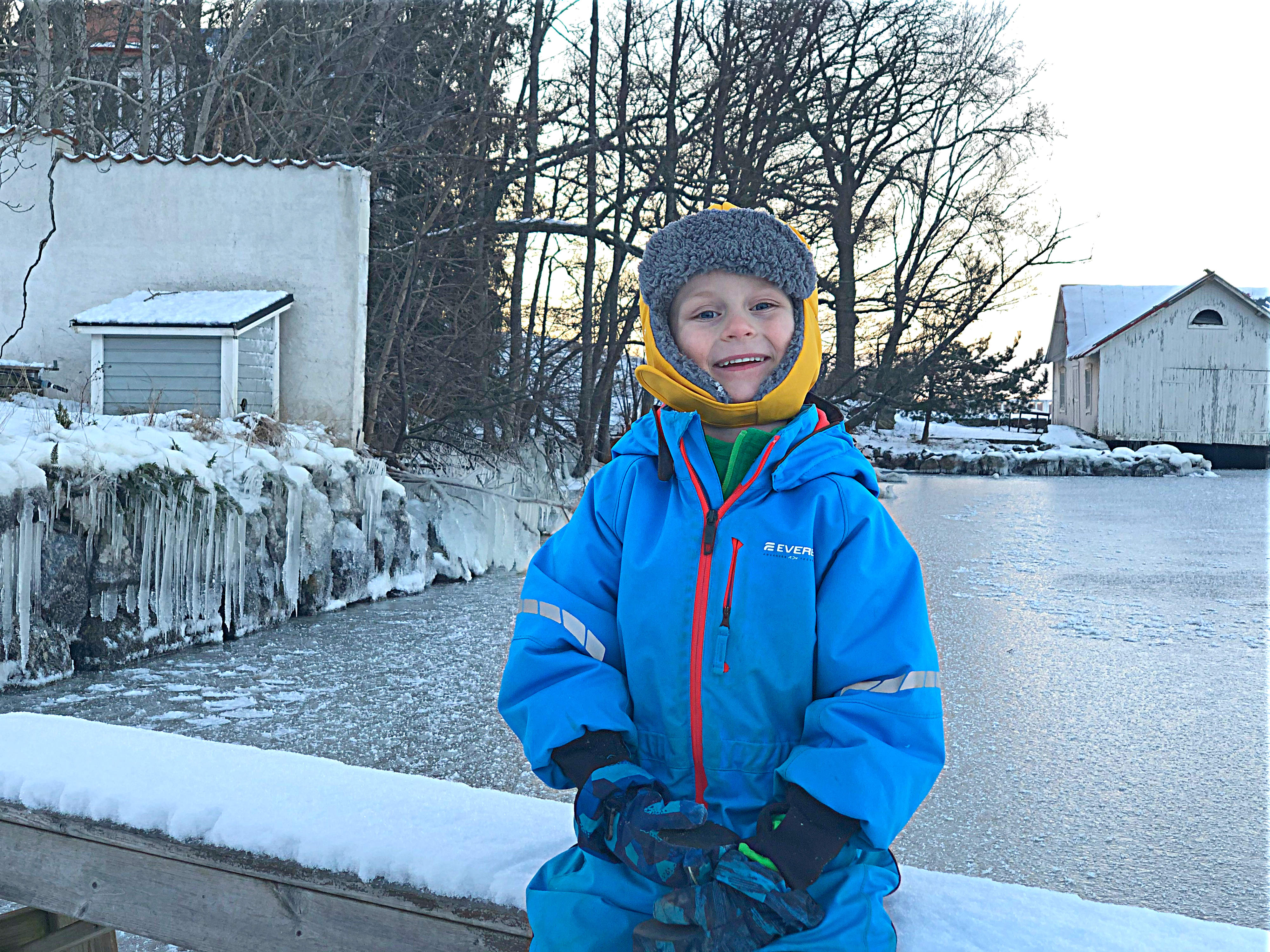 Glad pojke på brygga med is och snö i bakgrunden